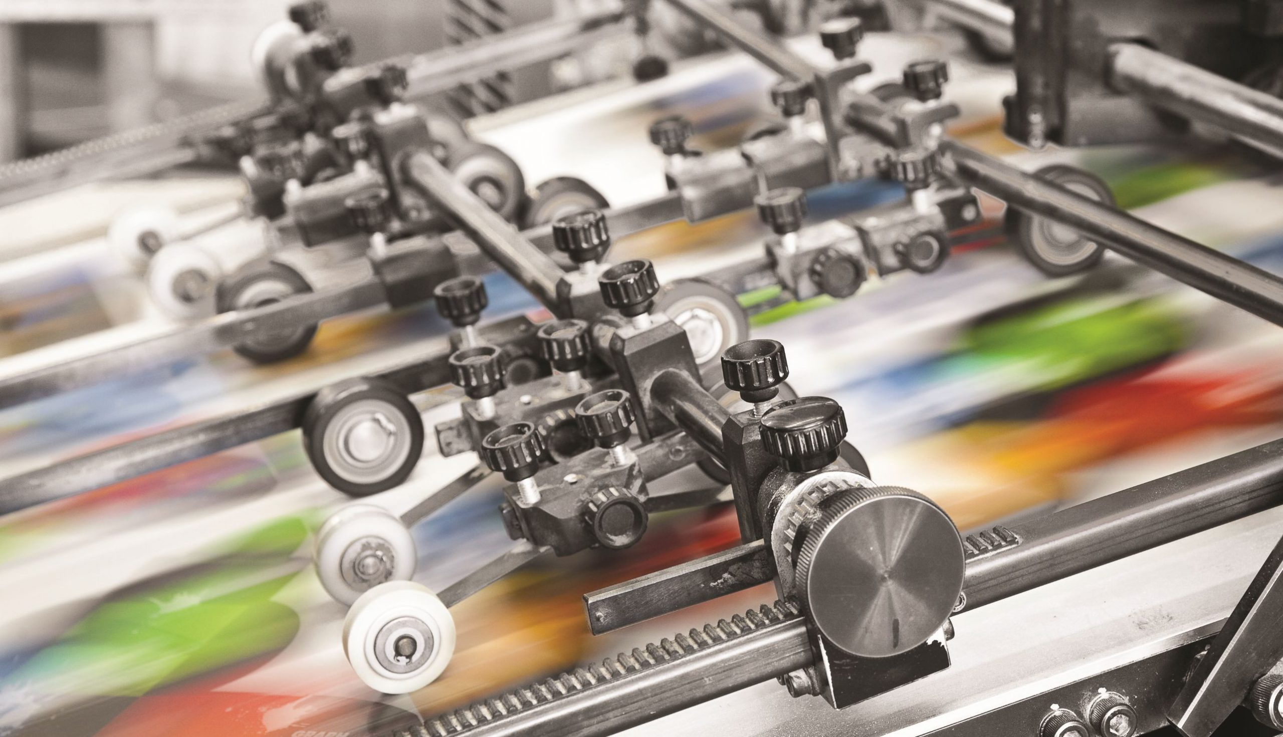 Close up of printing press creating coloured pages