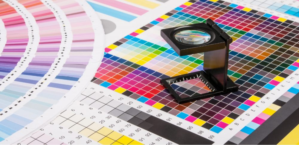 Close up of printing materials, showing magnifier, colour wheel and colour check print